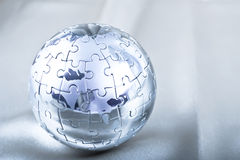 Metal Puzzle Globe. Vibrant Color Metal Puzzle Globe On Satin Royalty Free Stock Image
