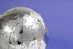 Metal puzzle globe on blue background Royalty Free Stock Images