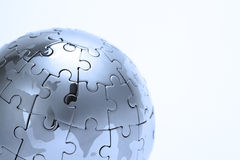 Metal puzzle globe, close-up in blue light Stock Photo