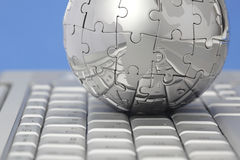 Metal puzzle globe on computer keyboard Stock Images
