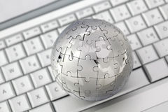 Metal puzzle globe on keyboard Royalty Free Stock Photography