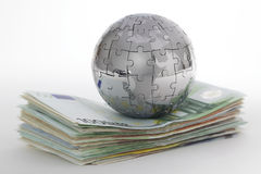 Metal puzzle globe with money Stock Photos