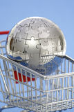 Metal puzzle globe with shopping cart Stock Images