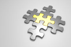Metal puzzle pieces on a white floor Stock Photo