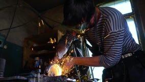 Metal que asierra del herrero profesional con la sierra de circular de los barehands en la fragua metrajes