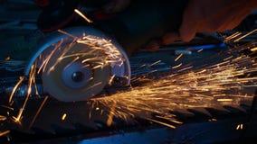 Metal que asierra del herrero profesional con la sierra de circular de los barehands en la fragua almacen de metraje de vídeo