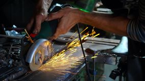 Metal que asierra del herrero profesional con la sierra de circular de los barehands en la fragua almacen de video