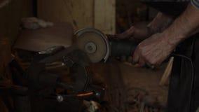 Metal que asierra del herrero profesional con la sierra de circular de la mano en la fragua almacen de video
