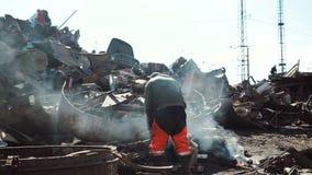 Metal que recicla, metal oxidado dos cortes do trabalhador com um cortador do gás em uma sucata vídeos de arquivo