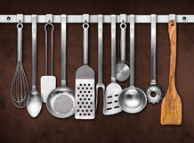 Metal rail with kitchen tools. Metal rail with kitchen utensils hanging in front of a colorful wall Royalty Free Stock Image
