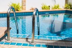 Metal rail ladder into swimming pool Royalty Free Stock Photography