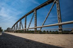 Metal railings on the bridge on sunny day. Road with c. Old rusty metal railings on the bridge on sunny day. Road with cracked asphalt stock image