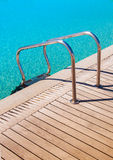 Metal railings in the pool near the wooden flooring Stock Image