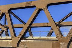 A metal railway bridge with a clear blue sky through the beams stock images