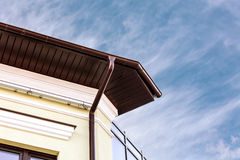 Metal rain gutter white downspout on corner of house Royalty Free Stock Photos
