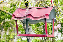 Metal red feeder for birds. Green background. Royalty Free Stock Photo