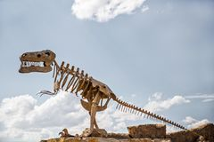 Metal replica of a dinosaur. A replica of a huge dinosaur made out of metal standing on rocks against a desaturated blue cloudy sky royalty free stock images