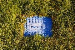 Metal ridged pokrywa z wodą na nim sadzał w trawie zdjęcie stock