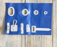 Blue tarpaulin with eyelet. Metal ring or grommet on a vinyl banner, secured with a zip tie. Riveted steel eyelet used for hanging banners, detail with a zip tie royalty free stock photo