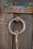 Metal ring lock with chain on a wooden door close-up. Metal round forged ring lock with metal large chain on a wooden door with a close-up bolt Royalty Free Stock Photography