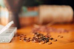 Metal rings on wooden table, closeup, needlework. Little metal rings on wooden table, closeup. Handmade jewelry. Needlework, bijouterie making Stock Photography
