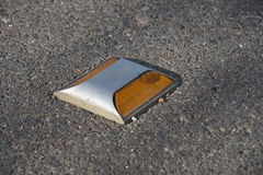 Metal road stud with yellow reflector on asphalt road in Thailand Stock Photos