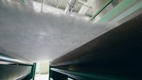Metal rollers move a layer of polyester batting at a factory. stock footage