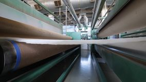 Metal rollers move white polyester fabric while working at a plant. stock video footage