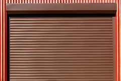 The Metal rollers shutters. The Metal rollers shutters horizontal brown color, closed shutters close-up stock photos
