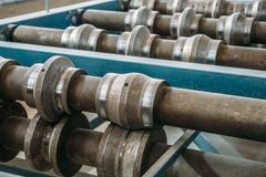 Metal rolls of roll forming machine close up at sandwich panel factory or metalwork manufacturing Stock Image