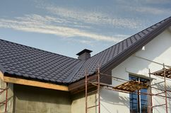 Metal roof construction with coaxial chimney pipe heating system against blue sky.  stock photography
