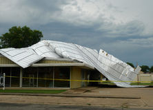 Metal roof storm damage, commercial building. Yellow police tape surrounds this building following a severe storm that lifted and removed a metal roof. Repairs stock photos