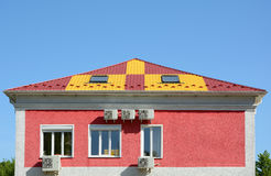 Metal roofing construction. House with a mansard and skylight windows. Rain gutter and snow guard. A multi-colored metal roof. And many air conditioners royalty free stock image