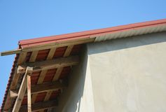 Metal roofing construction with unfinished eaves, fascia board. Soffits stock image
