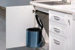 Metal rubbish bin under sink hanging on kitchen cupboard door stock image