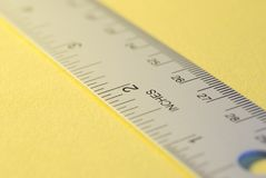 Metal_ruler-01. A metal ruler with selective focus on a yellow background Royalty Free Stock Image