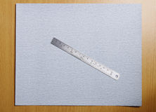 Metal ruler on sandpaper Royalty Free Stock Photos
