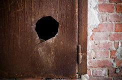 Metal rusted door with hole. Fragment of a metal rusted door with hole Royalty Free Stock Photo