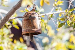 Metal rusty bell. Metal rusty bell hanging from tree branch on blurred background - spirituality concept stock photography