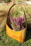 A metal rusty female handbag with tassels and a flower of heather on a background of yellow grass. Vertically royalty free stock images