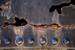 Metal with rusty hole and flaking paint Stock Images