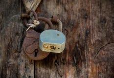 Metal rusty padlock on a closed old wooden door Stock Image