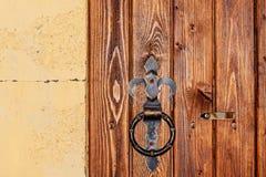 Metal rusty round handle on wooden door Royalty Free Stock Photography