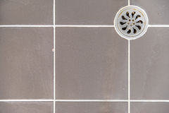 Metal rynsztokowa dziura w brudnej kafelkowej podłoga Obrazy Royalty Free