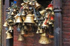Metal sacrificial bells at Kumbeshwar Temple, Nepal Stock Photography
