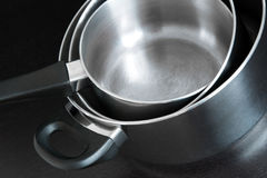 Metal saucepans on dark background Royalty Free Stock Image