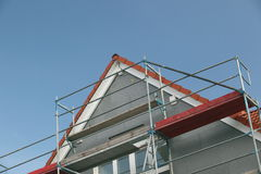 Metal scaffolding. On the side of a house near the roof peak royalty free stock photos