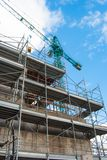 Scaffoldings and tower crane in a construction site stock images