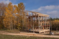 Metal scaffolding around the unfinished house. Construction of ecological house. Wooden frame of house under construction. Royalty Free Stock Images