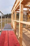 Metal scaffolding around the unfinished house. Construction of ecological house. Wooden frame of house under construction. Stock Image